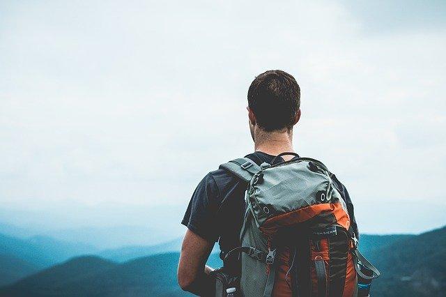 Viajero mirando al horizonte de espaldas con su mochila a cuestas